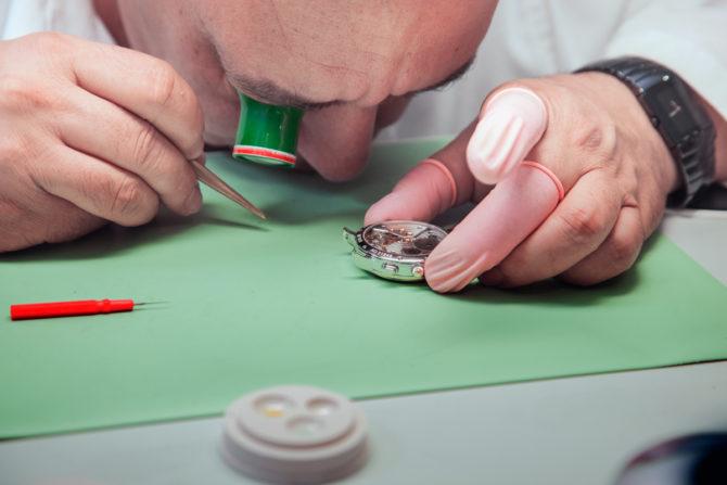 Един от часовникарите на Guilian прави профилактика на часовник на Maurice Lacroix докато носи Rado